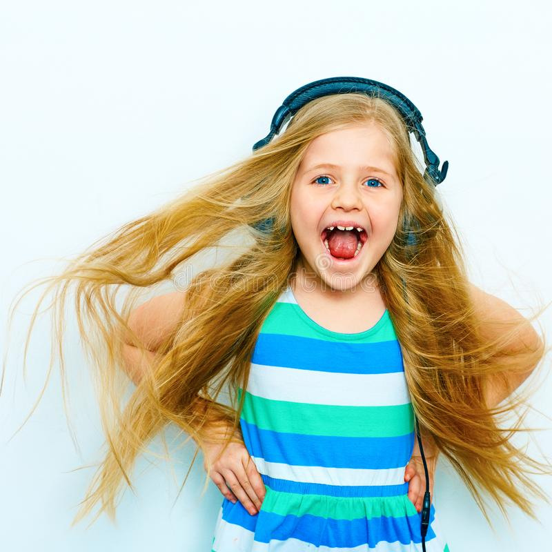 Screaming little girl with headphones funny portrait isolated o royalty free stock images