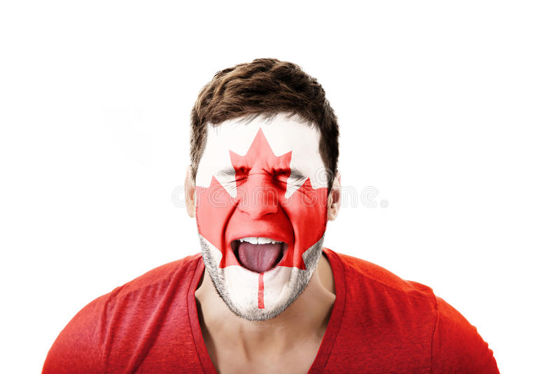 Screaming man with Canada flag on face. royalty free stock images