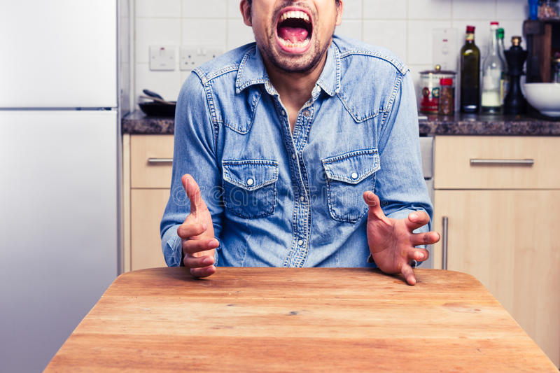 Screaming Man Gesturing With Hands In His Kitchen Stock