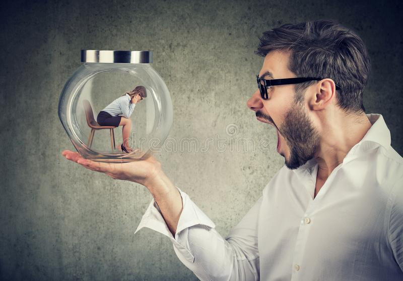 Screaming man holding glass jar with woman inside stock photography
