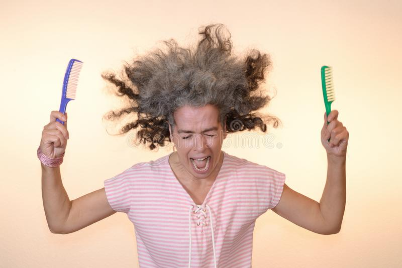 Bad hair day Screaming woman Flying hair. A screaming mature woman holding two combs, her hair flying up. Open mouth, shut eyes, graying hair, pink t-shirt royalty free stock images