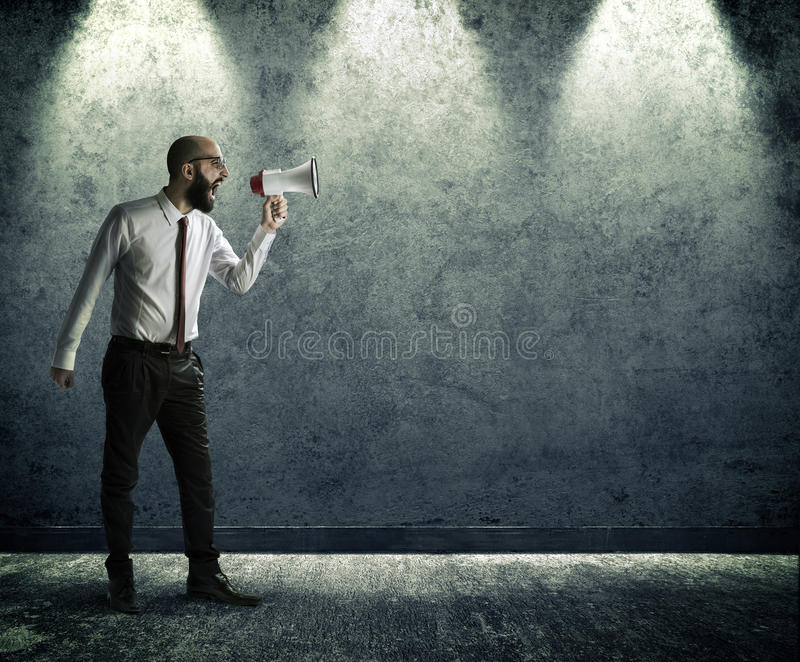 Screaming with megaphone. On the wall stock photo