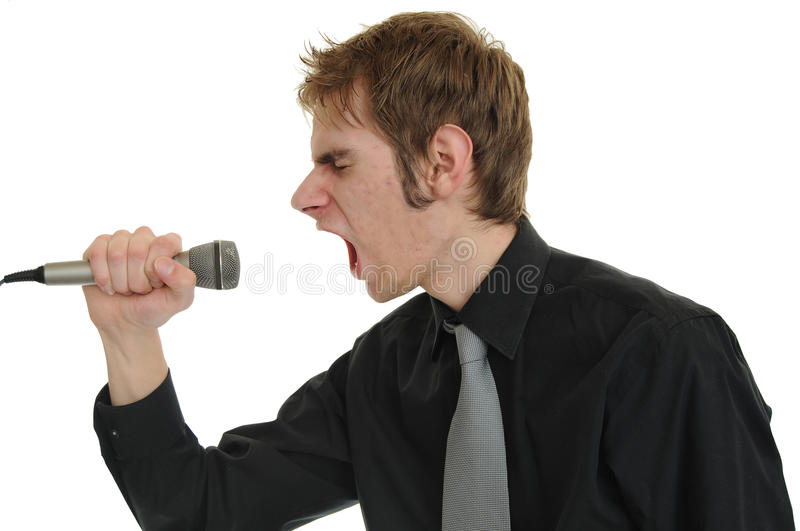 Screaming Into Microphone. Young man in a black suit and tie screams his emotional guts out into the microphone singing royalty free stock photo