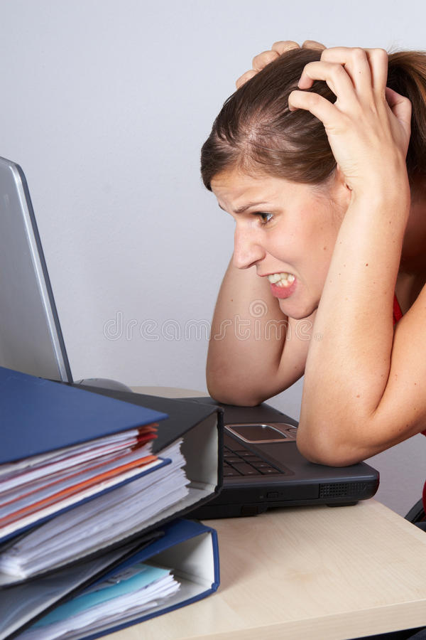 For screaming out loud. Young woman sitting at her laptop with a lot of work in front of her. She is very frustrated stock images