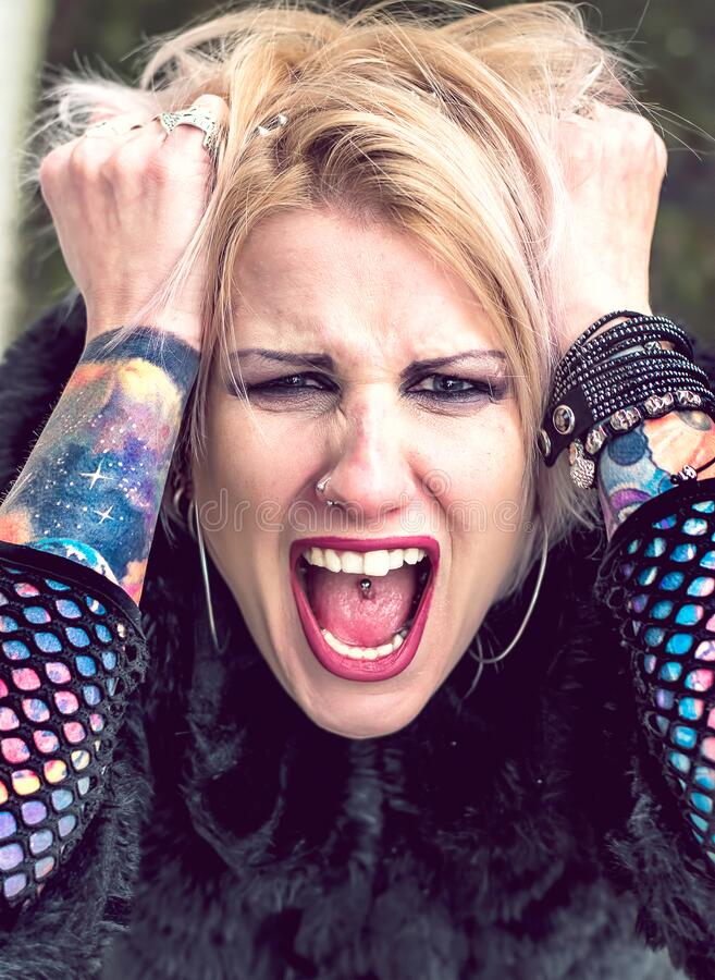 Screaming punk style woman with piercings and tattoos. Screaming angry blonde woman with piercings and tattoos stock photos