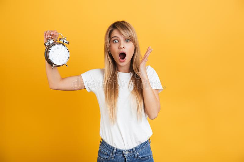 Screaming shocked young blonde woman posing isolated over yellow wall background dressed in white casual t-shirt holding alarm. Image of a screaming shocked royalty free stock photo
