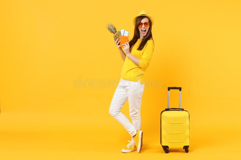 Screaming traveler tourist woman in hat hold passport, tickets, fresh pineapple fruit isolated on yellow orange. Background. Passenger traveling abroad on stock images