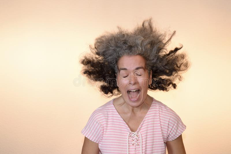 Bad hair day Screaming woman flying graying hair. A woman with open mouth, shut eyes, flying curly hair. Middle-aged woman, t-shirt, plain background stock photos