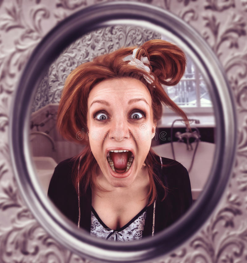 Screaming woman. Scared woman looks in th mirror screaming royalty free stock photo