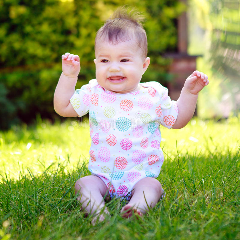 A screaming and wriggling baby in a vest sitting on the grass