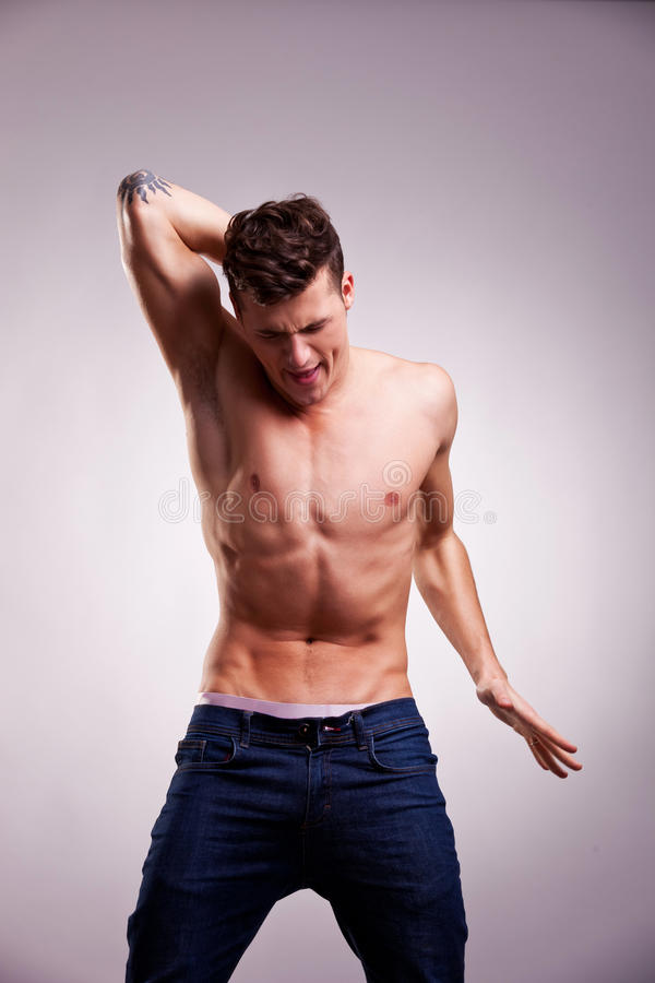Screaming young fit man in dance pose stock photos