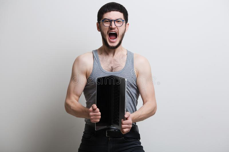 Screaming young guy opening laptop over white background. Wearing t-shirt and black jeans stock photo