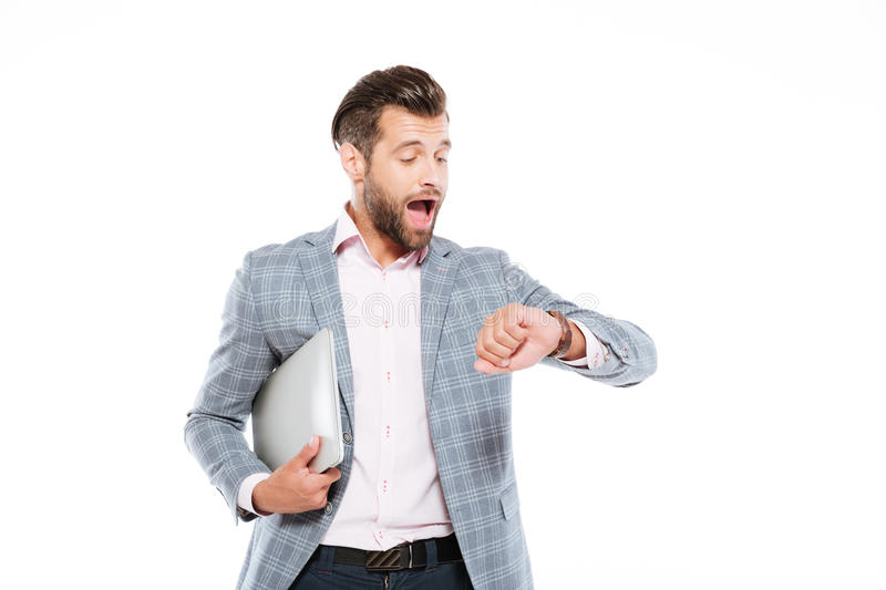 Screaming young man holding laptop computer looking at watch. Image of screaming young man standing isolated over white background and holding laptop computer stock photo