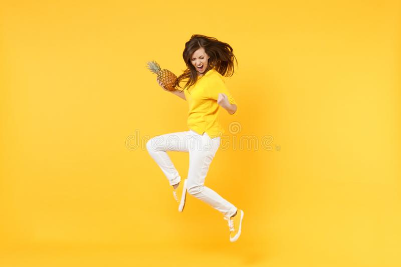 Screaming young woman in casual clothes doing winner gesture jumping hold fresh pineapple fruit isolated on yellow. Orange background. People vivid lifestyle royalty free stock image