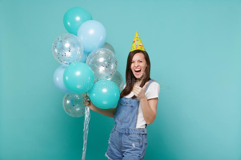 Screaming young woman in denim clothes, birthday hat showing thumb up celebrating, holding colorful air balloons. Isolated on blue turquoise background stock images
