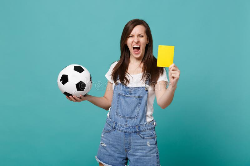 Screaming young woman football fan support team with soccer ball, yellow card, propose player retire from field isolated. On blue turquoise background. People stock images