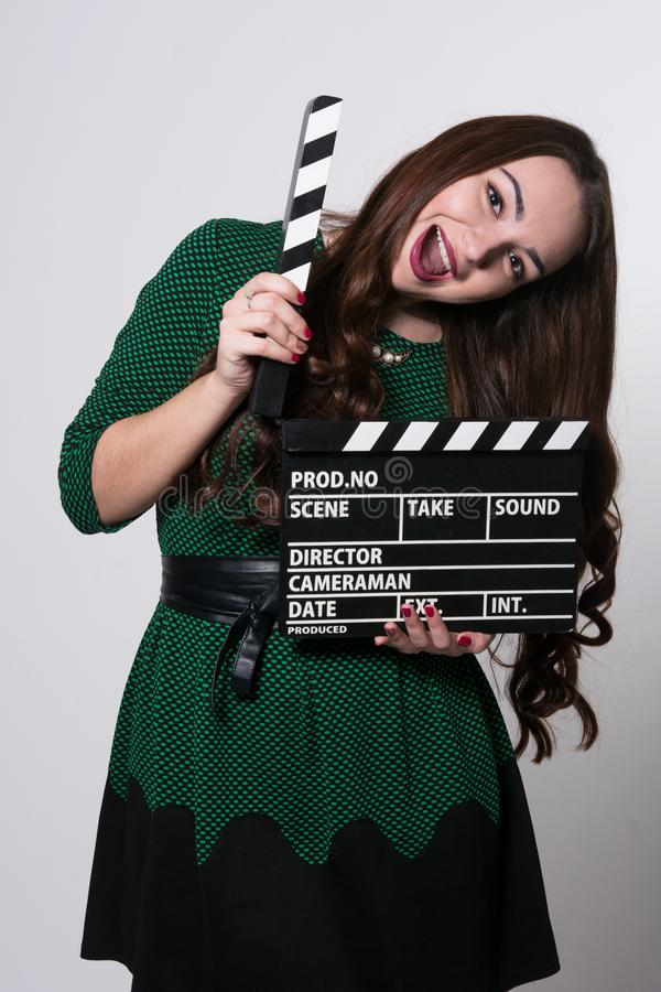 Screaming young woman holding a movie clapper. Girl in green dress helps in shooting a movie stock photography