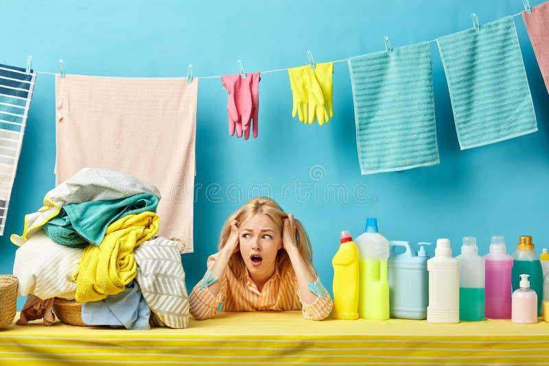 Scred surpreendeu a dona de casa que guarda sua cabeça, menina está receoso da roupa suja imagem de stock royalty free