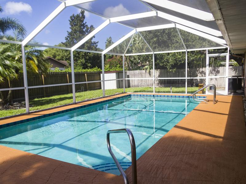 Screened pool attached to lanai. Swimming pool with cage attached to outdoor living space in sunny backyard royalty free stock images