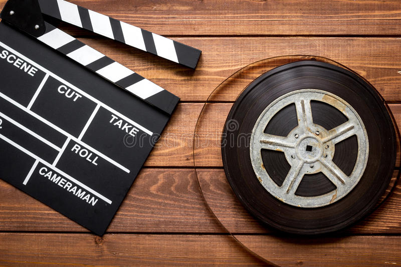 Screenwriter desktop with movie clapper board wooden background top view. Screenwriter desktop with movie clapper board on wooden background top view stock photography