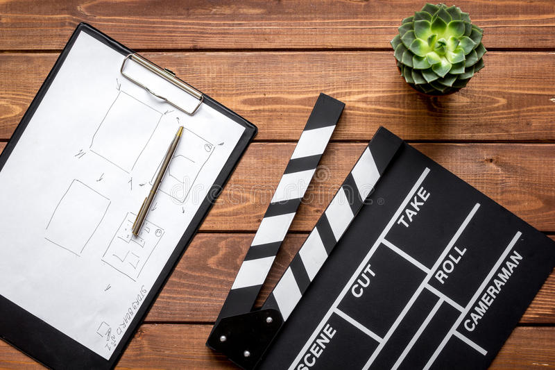 Screenwriter desktop with movie clapper board wooden background top view. Screenwriter desktop with movie clapper board on wooden background top view royalty free stock photos