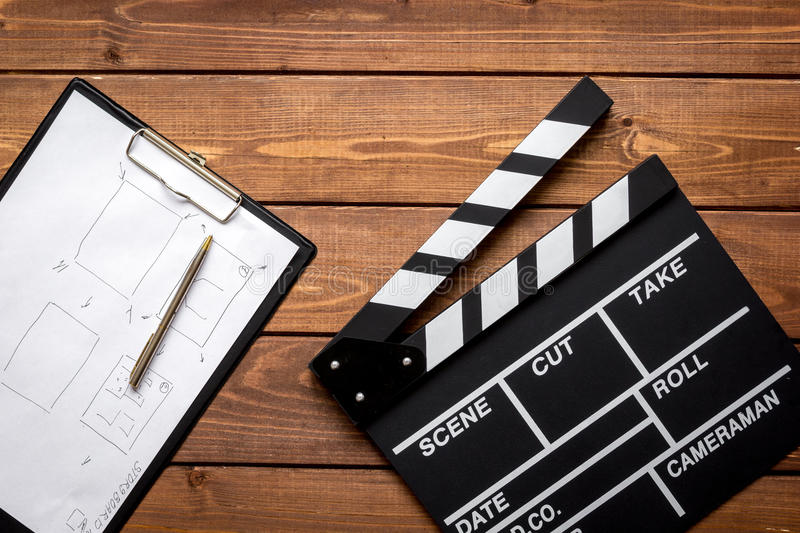 Screenwriter desktop with movie clapper board wooden background top view. Screenwriter desktop with movie clapper board on wooden background top view stock images