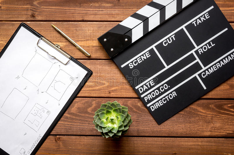 Screenwriter desktop with movie clapper board wooden background top view stock photography