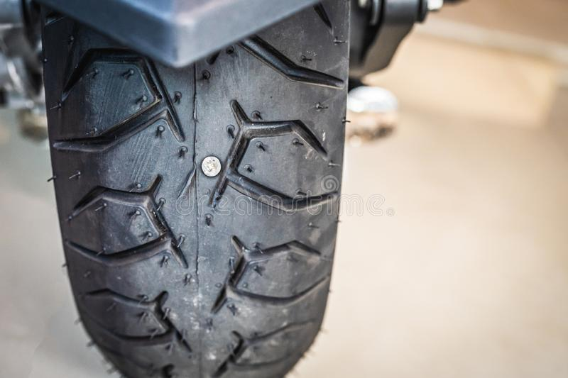 Nail or Iron stuck puncturing motorcycle or big scooter tire at a motorcycle repair shop. Selective focus.motorcycle repair. And service and maintenance concept royalty free stock photos