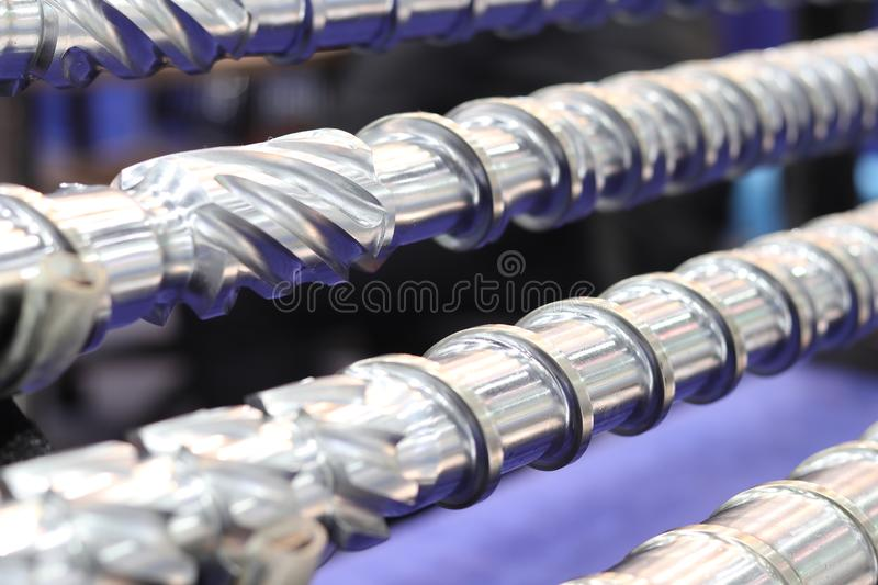 Screw press parts for plastic injection machine. Selective focus steel metal industry process processing technology equipment industrial factory machinery royalty free stock photography