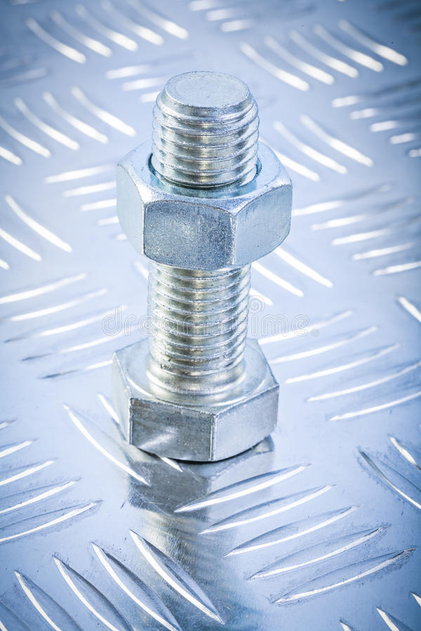 Screwbolt and threaded construction nut on corrugated metal back. Ground directly above royalty free stock image