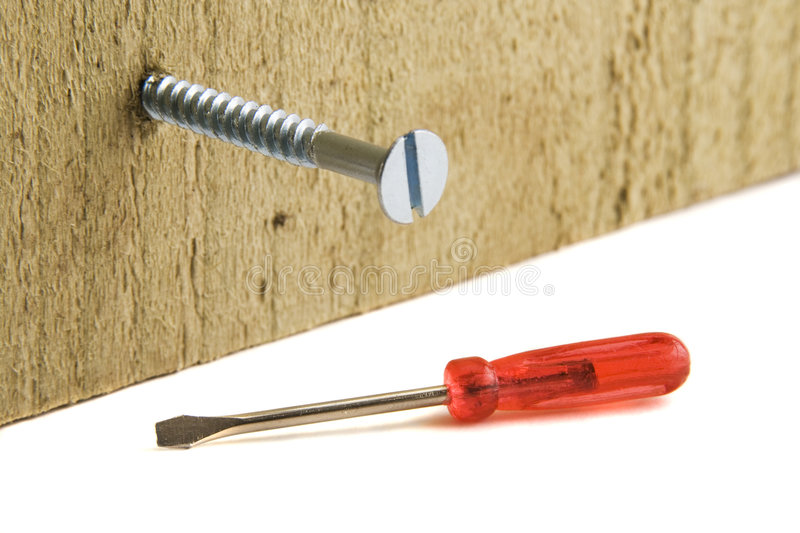 Screwdriver. A very small screwdriver lying on a white surface next to a large screw, screwed into a vertical piece of wood stock photos