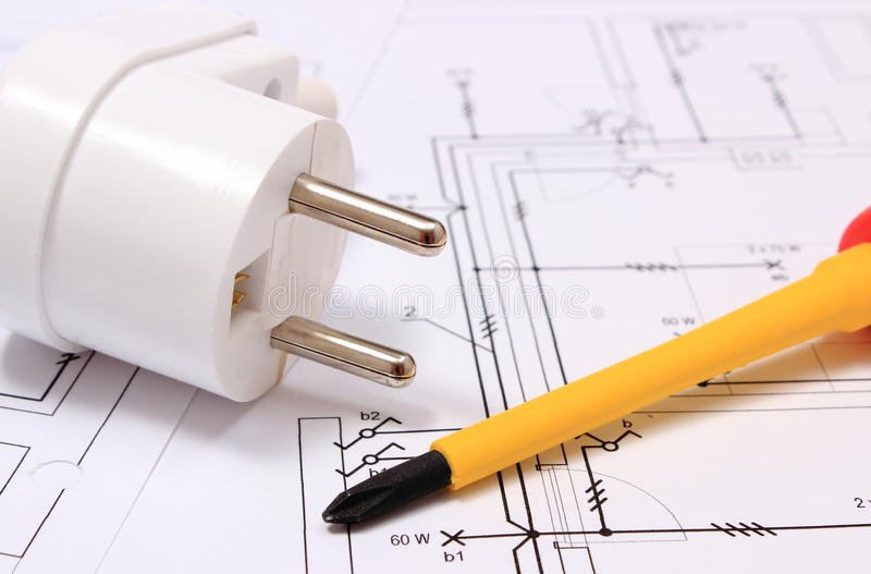 Screwdriver and electric plug on construction drawing. Screwdriver, work tools and electric plug lying on construction drawing of house, accessories for stock image
