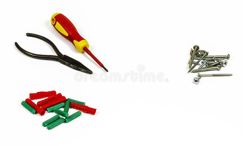 Screwdriver, pliers, screws and plastic dowels. On a white background stock photos