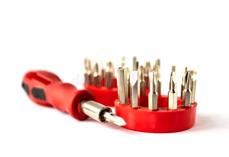 Screwdriver with a red handle and a set of bits on a white background. Screwdriver with red handle, set of screwdriver heads bits for tools, close-up, selective royalty free stock photos