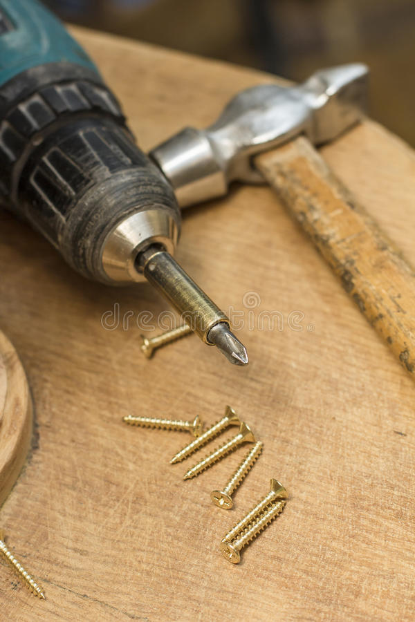 Screwdriver, screws and a hammer are on the table. Screwdriver, screws and a hammer are located an old desk stock photos