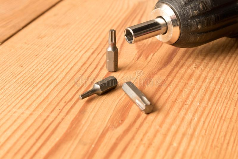 Screwdriver and a set of bits on a wooden table. The concept of work. Labor day.  royalty free stock photos