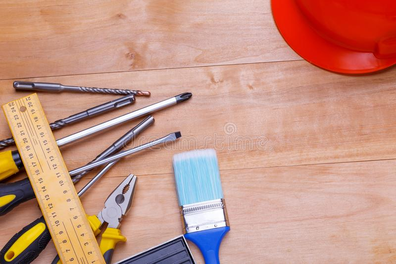 Tools and drills are shown in the left and a helmet in the right corner on a wooden background. View from above. Screwdriver tools are different, pliers, corner royalty free stock photos