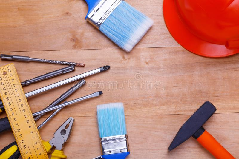 Tools in the left corner and drills, with a helmet and hammer on the right on a wooden background. View from above. Screwdriver tools are different, pliers royalty free stock images