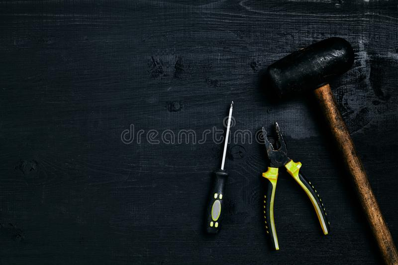 Screwdrivers, hammer, pliers and tools on a black wooden table. Top view royalty free stock photos