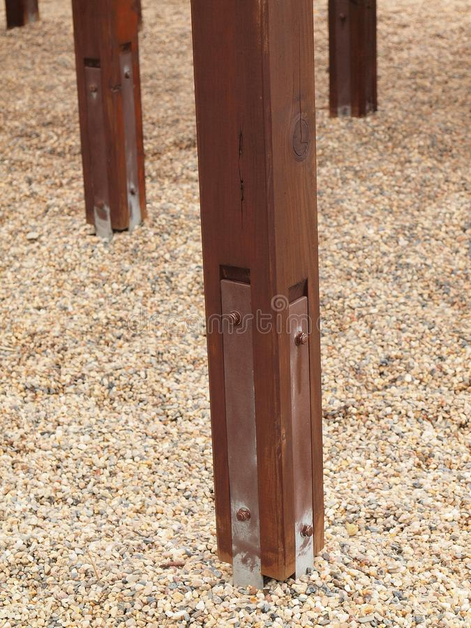 Screwed pole point of brown wooden construction. Detail of decreased iron screws and metal plates in outdoor brown equipment. Screwed pole point of brown wooden royalty free stock photo