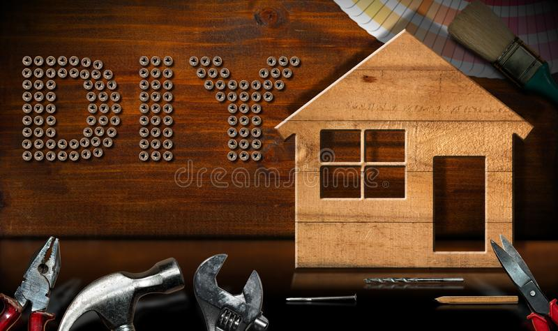 Diy Symbol - Work Tools and Model House. Screws in the shape of text Diy Do it yourself, wooden model house with work tools on a desk with reflections. Home royalty free stock image