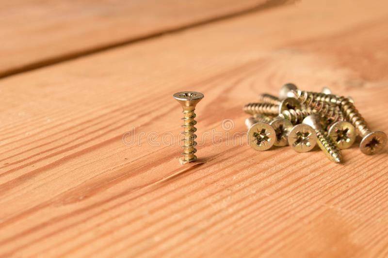 Screws on a wooden workbench. The concept of work.  stock photos