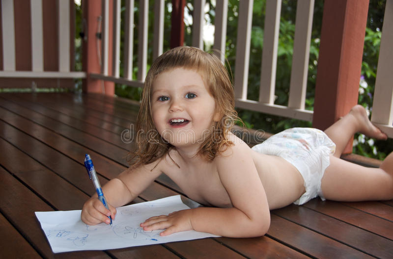 Scribbling Toddler. Toddler lying on her belly and developing her fine motor skills whilst proudly scribbling on a piece of paper royalty free stock photo