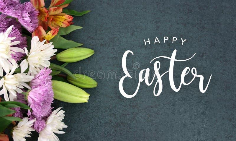 Scritto felice di festa di calligrafia di Pasqua con i fiori variopinti della primavera sopra struttura del fondo della lavagna fotografia stock