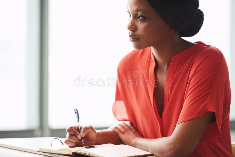Scrittore africano che cerca nella distanza mentre prendendo una rottura immagini stock libere da diritti