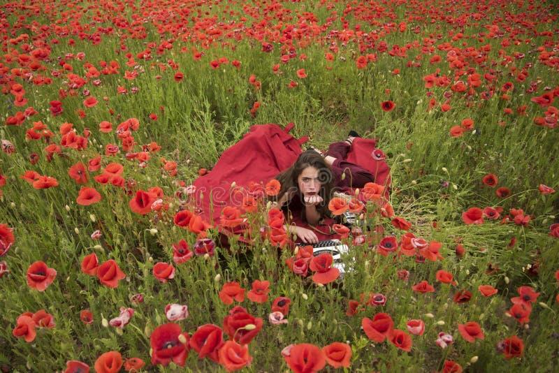 Scrittore della donna nel giacimento di fiore del papavero fotografia stock