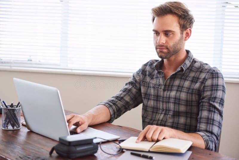 Scrittore occupato digitalizzando il suo lavoro dal taccuino scritto a mano al computer portatile immagine stock libera da diritti