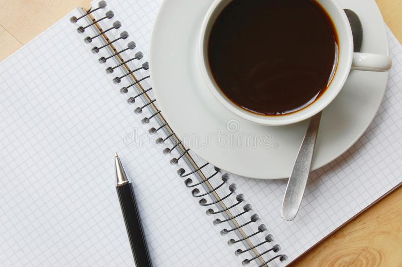 Scrittorio con caffè ed il taccuino immagini stock libere da diritti