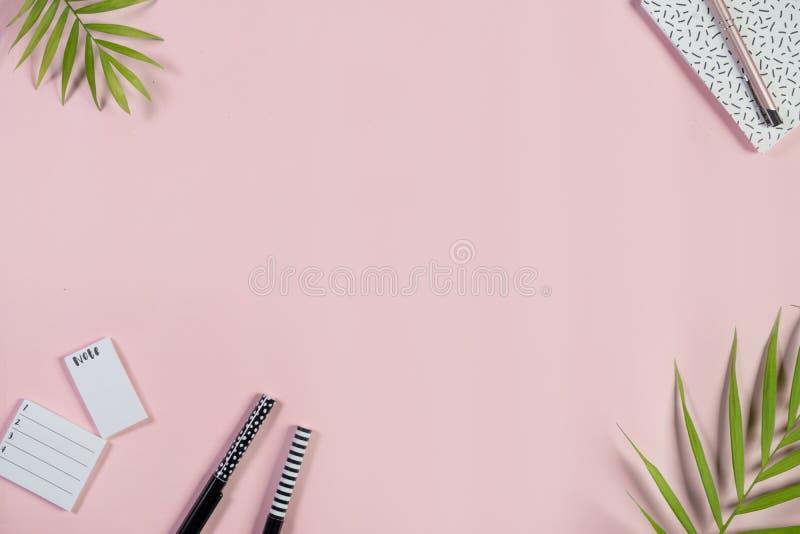 Scrittorio con il blocco note, la lista di da fare e le penne su un fondo rosa-chiaro Vista superiore fotografia stock