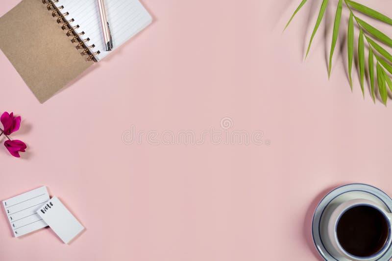 Scrittorio con il blocco note, la tazza di caffè e la penna sul fondo di rosa di bambino Vista superiore fotografie stock libere da diritti